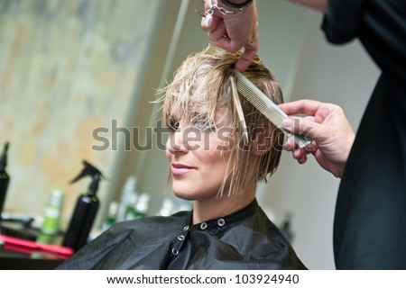 attractive woman in hair salon with cut hair on her shoulder
