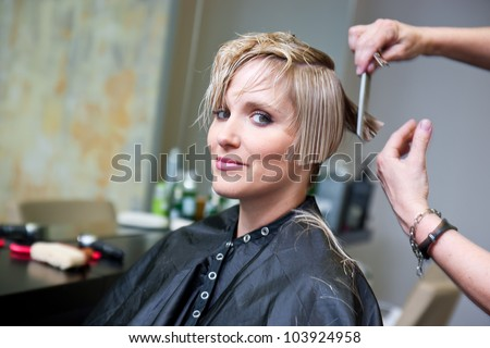 attractive woman in hair salon with cut hair on her shoulder - stock photo