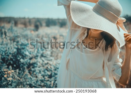 Attractive woman in hat with wide brim walking in fantastic park - stock photo