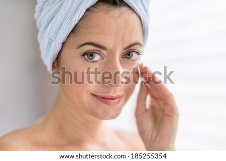 attractive woman in her forties removing make up - stock photo