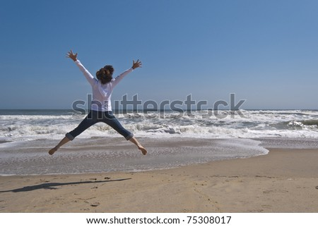 Attractive woman in her 40s is jumping for joy on a secluded beach. Image was taken at the Outer Banks in North Carolina