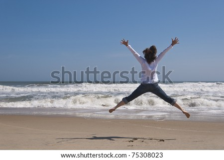 Attractive woman in her 40s is jumping for joy on a secluded beach. Image was taken at the Outer Banks in North Carolina - stock photo