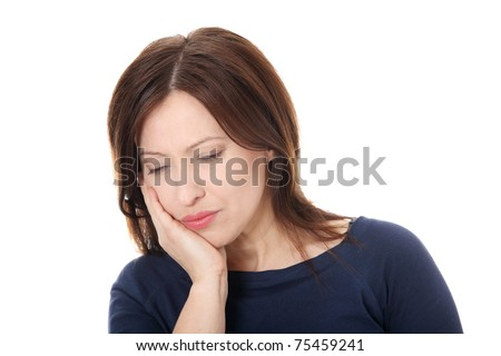 Attractive woman in her 40s pressing her bruised cheek with a painful expression as if she's having a terrible tooth ache. - stock photo