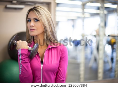Attractive Woman in her thirties with long blonde hair exercising with weights - stock photo