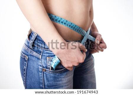 Attractive woman in jeans measuring waist with tape.