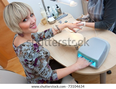 attractive woman in manicure salon polishing her nails by beautician