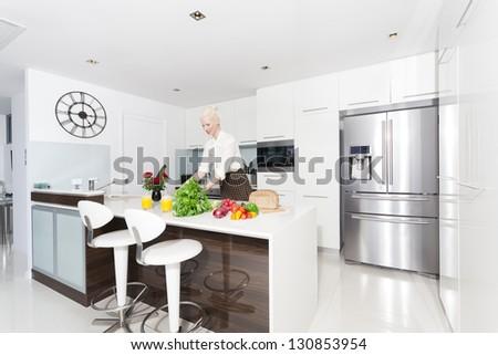 Attractive woman in modern kitchen - stock photo