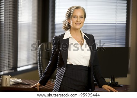 Attractive woman in office smiling for the camera. - stock photo