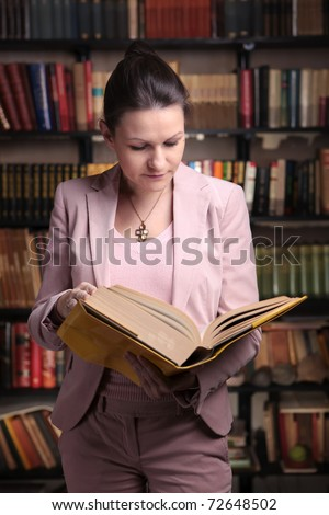 Attractive woman in pink suit reading book in library - stock photo