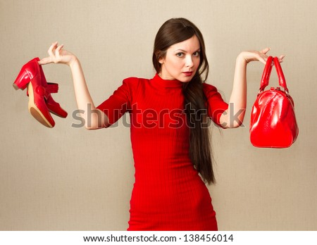 Attractive woman in red dress holding high heel shoes and handbag. - stock photo