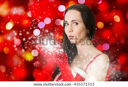 Attractive woman in Santa Clause costume blowing the Christmas wishes