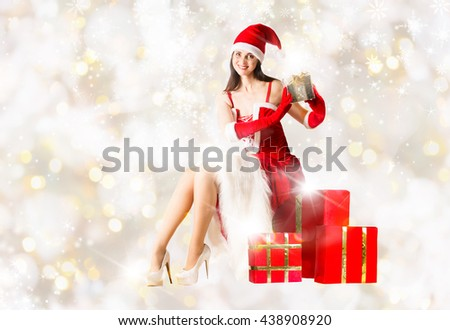 Attractive woman in Santa Clause outfit sitting on the present box and holding Christmas present. Christmas background - stock photo
