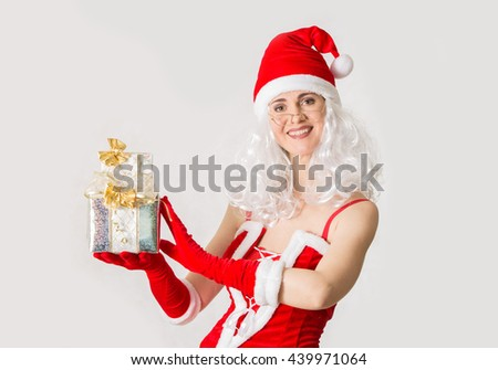 Attractive woman in Santa costume holding Christmas gifts - stock photo