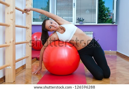 attractive woman in stretching pose in gym - stock photo