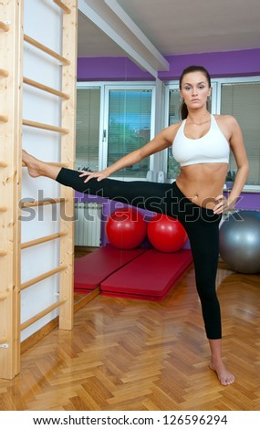 attractive woman in stretching pose on gym ladders - stock photo