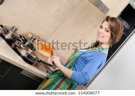 Attractive woman in striped apron slices vegetables in the modern comfortable kitchen