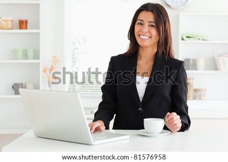 Attractive woman in suit enjoying a cup of coffee while relaxing with her laptop in the kitchen - stock photo