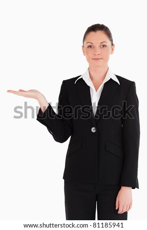 Attractive woman in suit showing a copy space while standing against a white background - stock photo