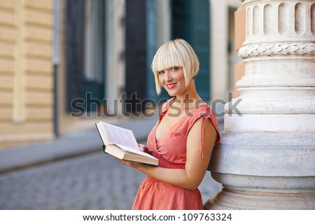 attractive woman in the city street with book - stock photo