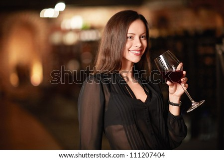 Attractive woman in the wine cellar - stock photo