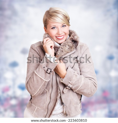 attractive woman in warm clothes in a winter scene  - stock photo