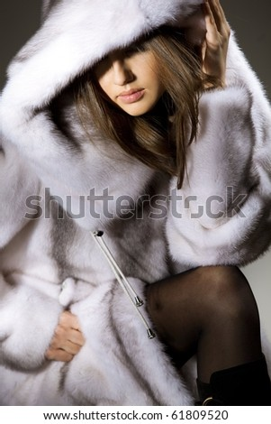 Attractive woman in white and gray fur coat with hood