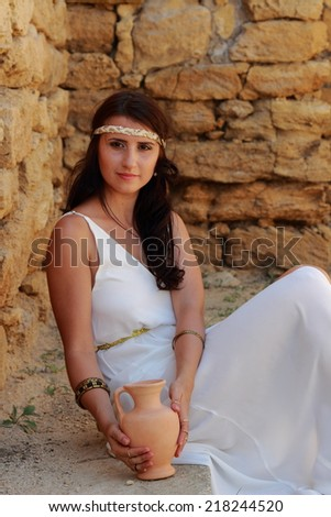 Attractive woman in white long dress in Greek style keeps ancient amphora background excavations of the ancient city as the ancient Greek goddess  - stock photo