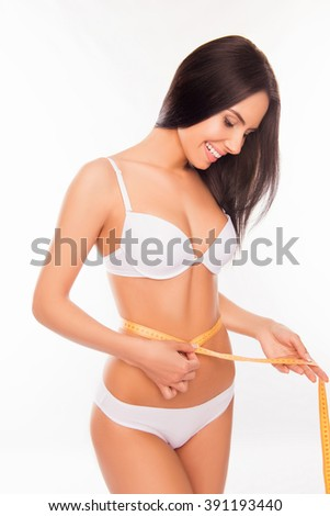 Attractive woman in white underwear measuring her waist with measuring tape