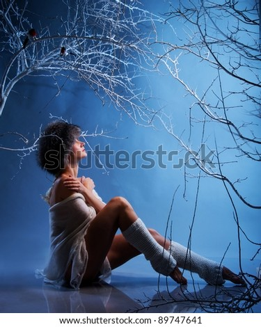 Attractive woman in winter forest - stock photo