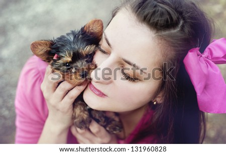 Attractive woman is giving a hug to her yorkshire puppy