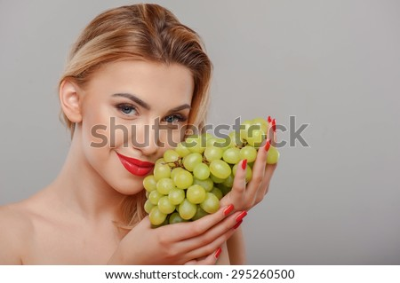 Attractive woman is holding a bunch of grapes and touching it to her cheek. She is gently smiling. Isolated on grey background and there is copy space in right side - stock photo