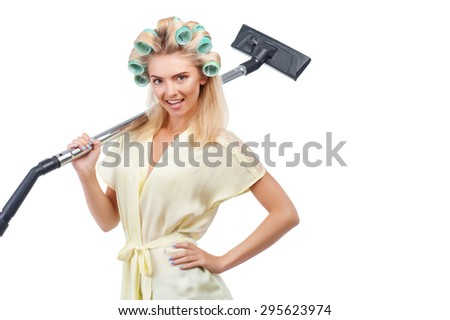 Attractive woman is holding vacuum cleaner. She is smiling and looking at the camera with enjoyment. Isolated on background and copy space in right side - stock photo