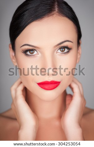 Attractive woman is looking at the camera with desire. She is touching her neck with both her hands flirtingly. Isolated on background - stock photo