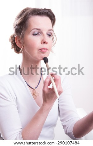 attractive woman is putting her make up on - stock photo
