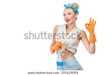 Attractive woman is showing okay sign and smiling. She is doing cleanup. The lady is holding spray. Isolated on background and copy space in left side - stock photo