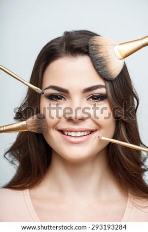 Attractive woman is smiling. Make-up brushes are around her face. Isolated on a grey background - stock photo