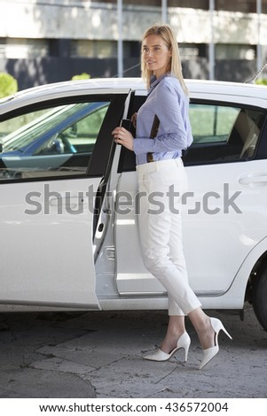 Attractive woman is standing near her car. She is opening the car door - stock photo
