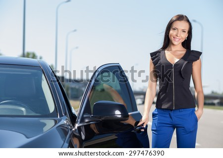 Attractive woman is standing near her car. She is opening the door and  holding the handle. The woman is smiling and looking forward. She is meeting her business partner - stock photo
