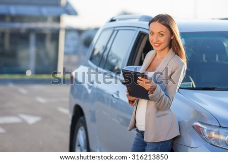 Attractive woman is standing near her car. She is using a tablet with interest. The lady is smiling and looking at the camera with joy. Copy space in left side - stock photo