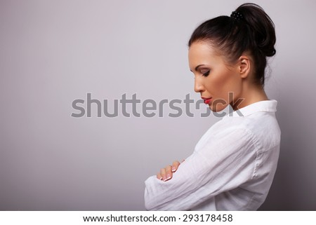 Attractive woman is tilting her head and looking down with offence. She crossed her hands. Isolated on grey background and there is copy space in left side - stock photo
