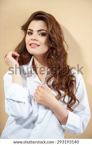 Attractive woman is unbuttoning clothing coquettishly. She is flirtingly twisting her curls and smiling. Isolated on brown background - stock photo