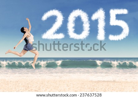 Attractive woman jumping on the beach celebrate new year of 2015 - stock photo