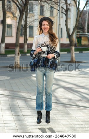 attractive woman jumps with white cup. happy smile girl holds coffee or tea cup.  city background - stock photo