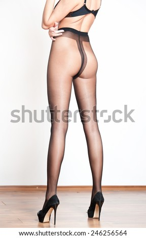 Attractive woman legs on high heels in black stockings posing challenging in room. Back side view of perfect body woman with long legs and high heels. Classic boudoir shot. Erotic photo. - stock photo