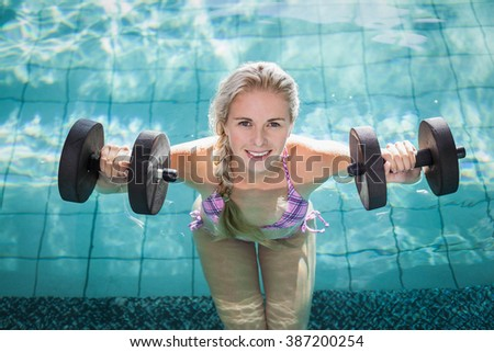 Attractive woman lifting dumbbells in the pool - stock photo