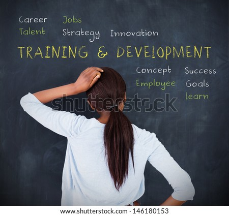 Attractive woman looking at a chalkboard with business terms written on it