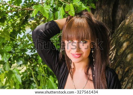 Attractive woman looking at camera on the background of fresh green tree leaves. She holding her long brown hair. Copy space.  - stock photo