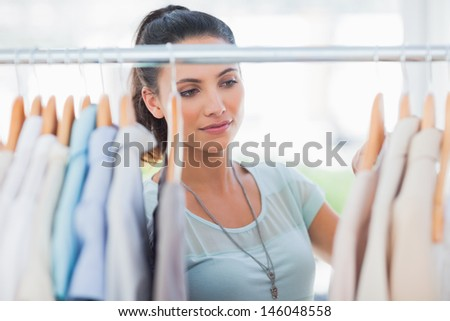 Attractive woman looking at clothes in a studio - stock photo