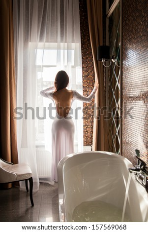 Attractive woman looking at window and preparing to take a bath - stock photo