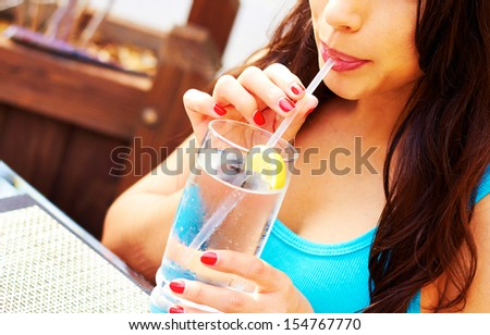 Attractive woman looking away while drinking fresh glass of water. Horizontal Shot. - stock photo